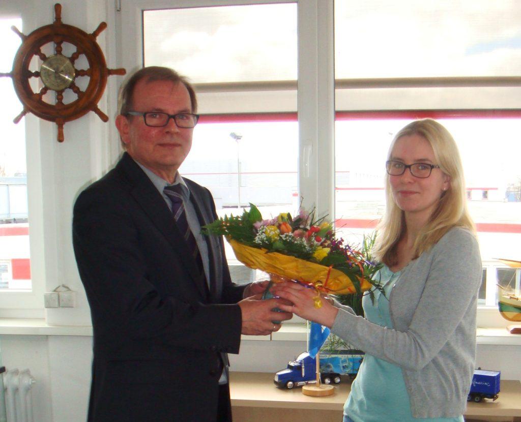 Abteilungsleiter Jürgen Finke überreicht in Namen des Hauses die Glückwünsche und den Blumenstrauß.